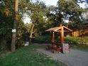 Večerní paprsky Slunce zalévají stříšku odpočívadla u lávky přes Svratku nad soutokem s říčkou Loučka.